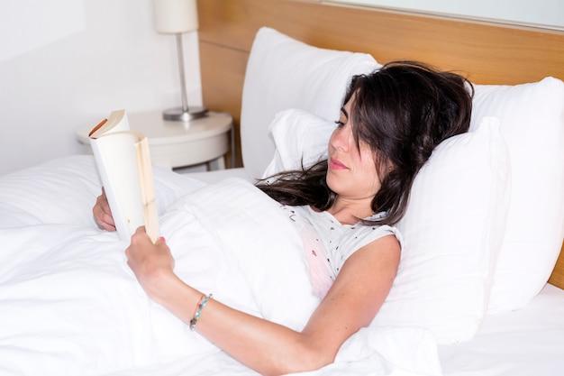 Femme lisant un livre avant d'aller dormir