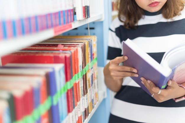 Femme lisant un livre à la bibliothèque, mise au point sélective