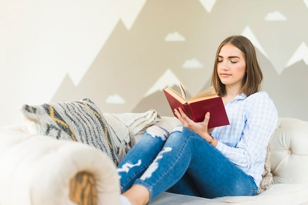 Femme lisant un livre sur le canapé dans le salon