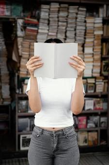 Femme lisant un livre dans une bibliothèque