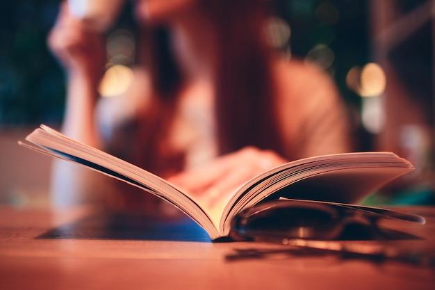 Femme lisant un livre dans un café.