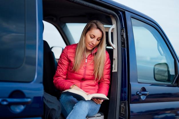 Femme lisant un livre dans la camionnette