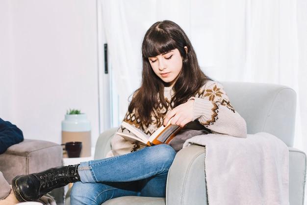Femme lisant un livre dans le fauteuil