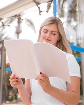 Femme lisant un livre à l'extérieur