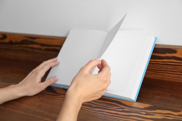 Femme lisant un livre intéressant à la maison