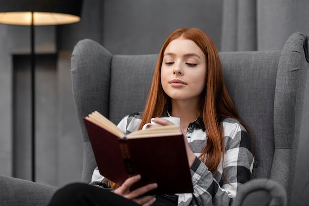 Femme lisant un livre à l'intérieur