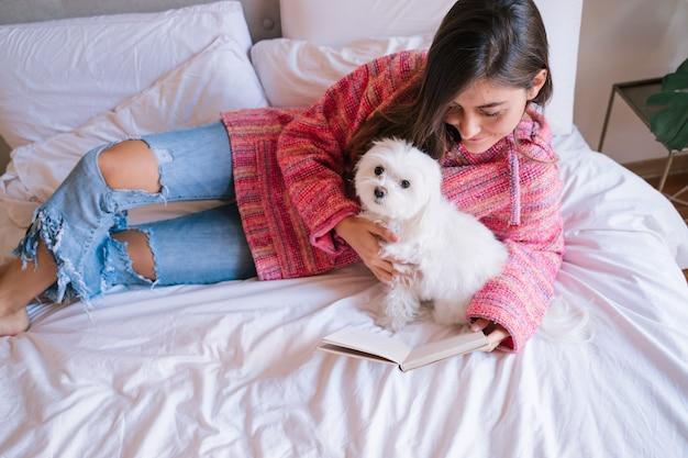 Femme lisant un livre sur le lit à la maison. chien maltais mignon en plus