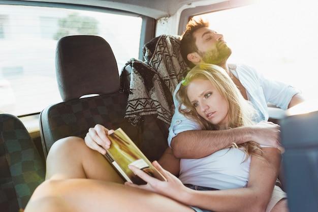 Femme lisant un livre près de l'homme qui dort