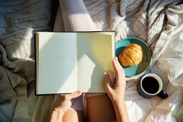 Femme lisant un livre roman sur le lit petit déjeuner