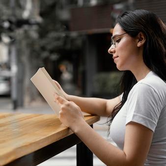 Femme lisant un livre seule