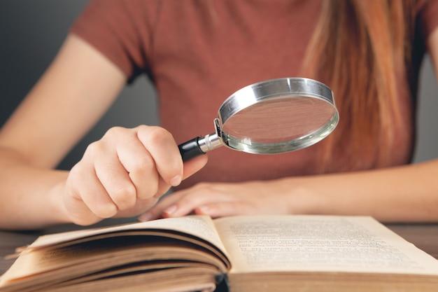 Femme lisant un livre à la table avec une loupe