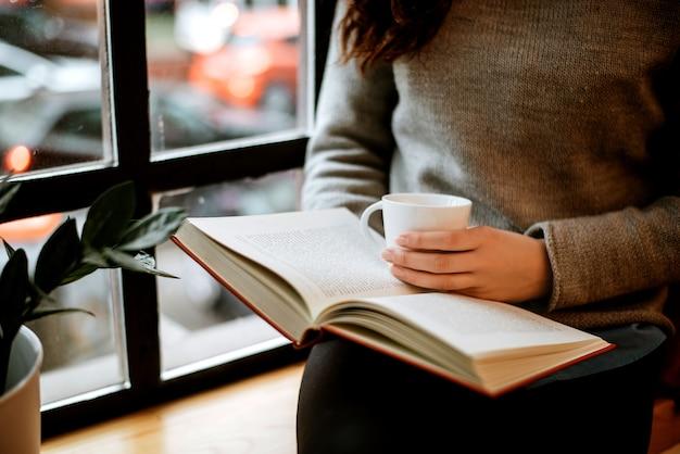 Femme lisant un livre et tenant une tasse de café.