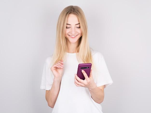Femme lisant un message texte sur son téléphone, isolé sur fond blanc.
