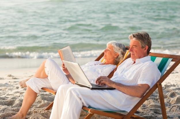 Femme lisant pendant que son mari travaille sur son ordinateur portable