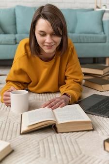 Femme lisant sur le plancher plein coup