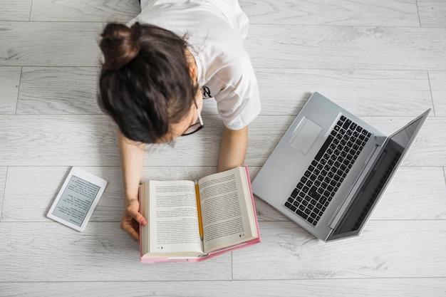 Femme lisant près d'ordinateur portable et e-book