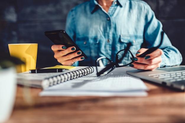 Femme lisant un sms sur un téléphone intelligent