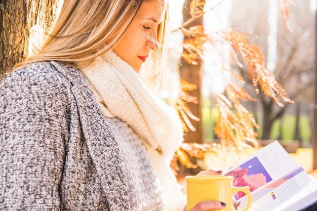 Femme lisant à la surface de l'automne