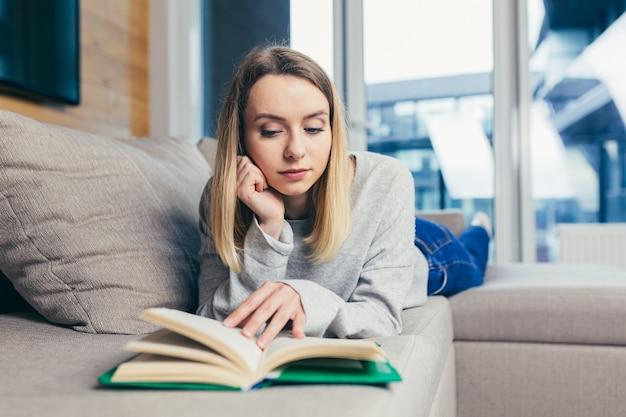 Femme lit un livre intéressant en position allongée sur le canapé se reposant après le travail