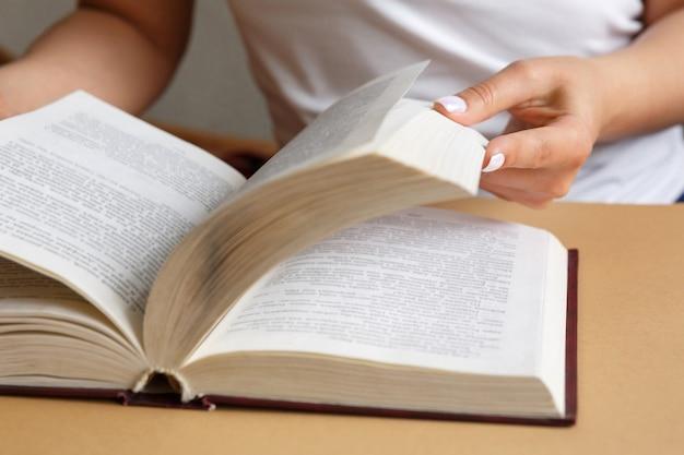 Femme lit un livre les mains tiennent un livre belle manucure l'étudiant étudie le manuel concept d'éducation et d'étude de l'information