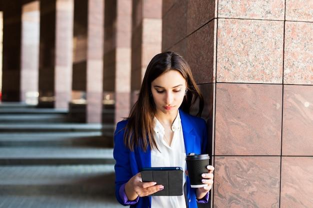 La femme lit quelque chose dans la rue avec une tasse de café