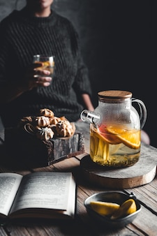 Femme lit et thé chaud avec pamplemousse frais sur tablette en bois. boisson saine, eco, végétalienne.