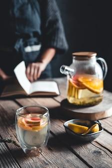 Femme lit et thé chaud avec pamplemousse frais sur tablette en bois