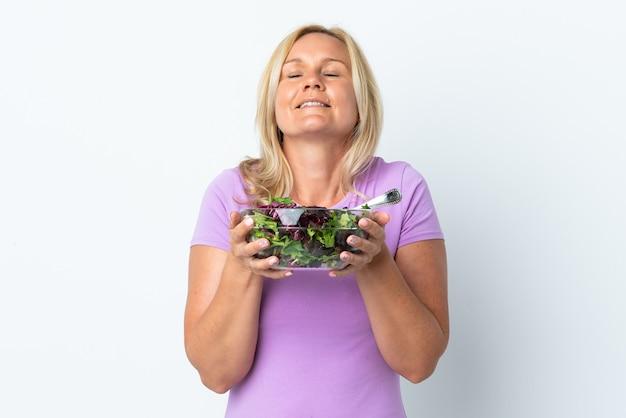 Femme lituanienne d'âge moyen isolée sur mur blanc tenant un bol de salade avec une expression heureuse