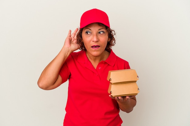 Femme de livraison d'âge moyen prenant des burguers isolés sur fond blanc essayant d'écouter un potin.