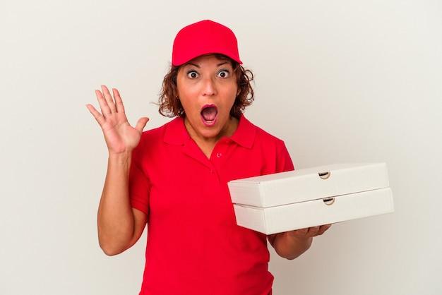 Femme de livraison d'âge moyen prenant des pizzas isolées sur fond blanc surprise et choquée.