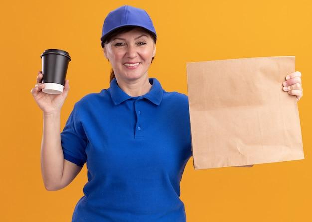 Femme de livraison d'âge moyen en uniforme bleu et cap holding paper package montrant tasse de café à l'avant avec sourire sur le visage debout sur le mur orange
