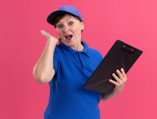 Femme de livraison d'âge moyen en uniforme bleu et cap holding presse-papiers à l'avant heureux et surpris debout sur le mur rose