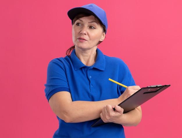 Femme de livraison d'âge moyen en uniforme bleu et cap holding presse-papiers et crayon à côté avec une expression confiante sérieuse debout sur un mur rose