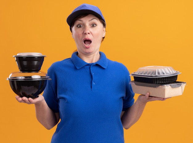 Femme de livraison d'âge moyen en uniforme bleu et cap tenant des paquets de nourriture à l'avant étonné et surpris debout sur un mur orange