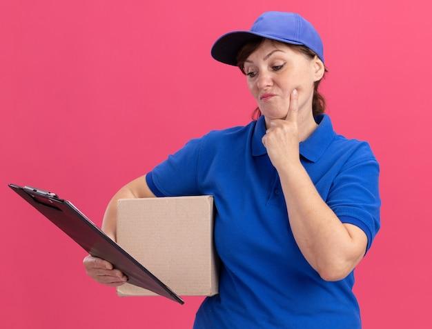 Femme de livraison d'âge moyen en uniforme bleu et casquette tenant une boîte en carton à la planchette avec un visage sérieux debout sur un mur rose