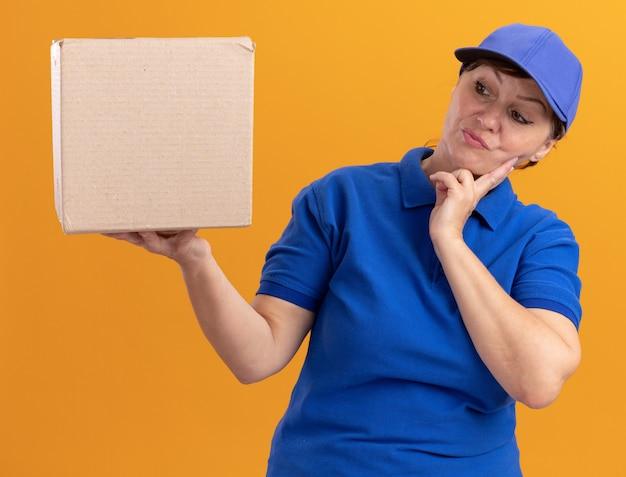 Femme de livraison d'âge moyen en uniforme bleu et casquette tenant une boîte en carton à la regarder perplexe debout sur un mur orange