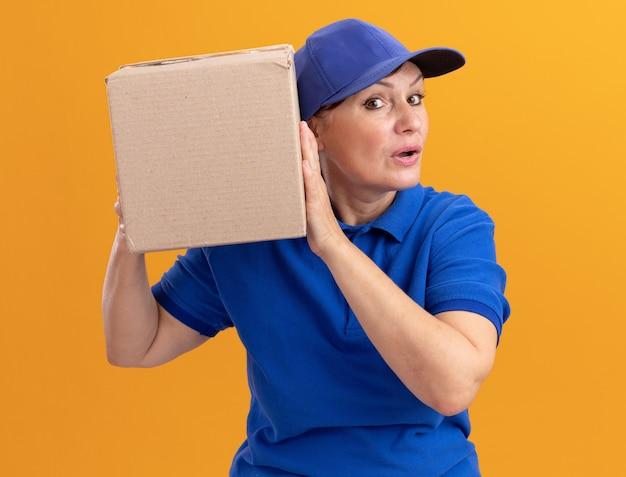 Femme de livraison d'âge moyen en uniforme bleu et casquette tenant une boîte en carton sur son oreille à l'écoute debout sur un mur orange