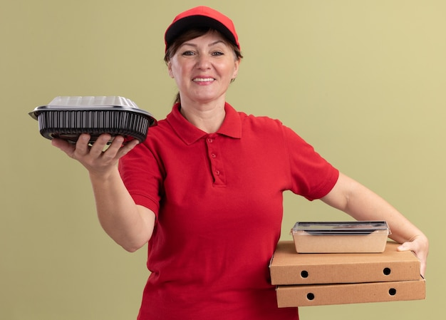 Femme de livraison d'âge moyen en uniforme rouge et cap tenant des boîtes de pizza et des emballages alimentaires à l'avant souriant confiant debout sur mur vert