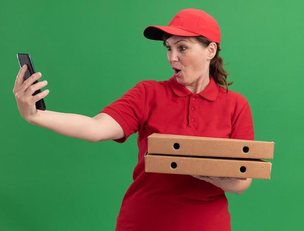 Femme de livraison d'âge moyen en uniforme rouge et cap tenant des boîtes de pizza à la recherche de smartphone à être surpris et confus debout sur le mur vert