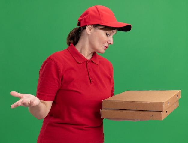 Femme de livraison d'âge moyen en uniforme rouge et cap tenant des boîtes de pizza en les regardant confus debout sur mur vert