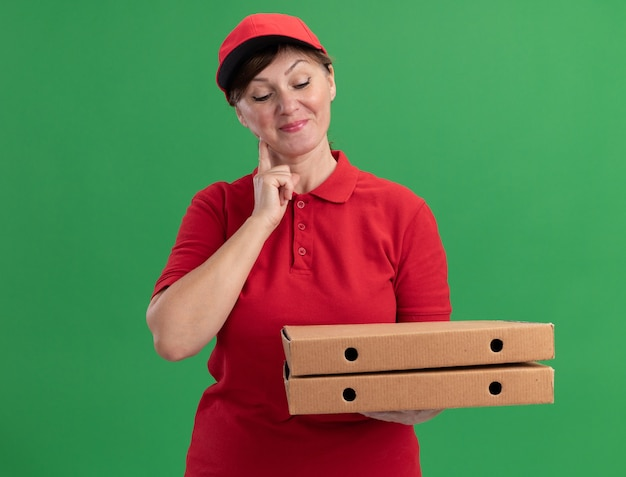 Femme de livraison d'âge moyen en uniforme rouge et cap tenant des boîtes de pizza en les regardant avec le sourire sur le visage heureux et positif debout sur le mur vert