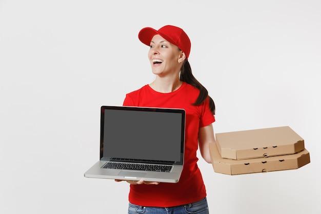 Femme de livraison au bonnet rouge, t-shirt donnant une commande de nourriture pizza italienne dans des boîtes en carton plates isolées sur fond blanc. courrier féminin tenant un ordinateur portable avec un écran vide noir vide.