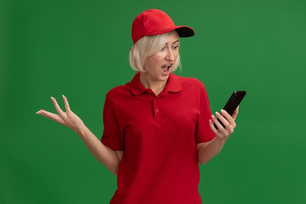 Femme de livraison blonde d'âge moyen agacée en uniforme rouge et casquette tenant et regardant un téléphone portable montrant une main vide isolée sur un mur vert