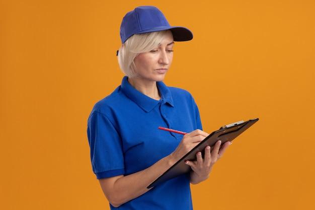 Femme de livraison blonde d'âge moyen concentrée en uniforme bleu et casquette écrivant sur le presse-papiers avec un crayon regardant le presse-papiers isolé sur un mur orange avec espace de copie