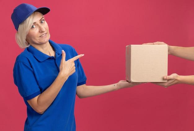 Femme de livraison blonde d'âge moyen impressionnée en uniforme bleu et casquette donnant une boîte en carton au client pointant vers elle