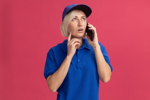 Femme de livraison blonde d'âge moyen impressionnée en uniforme bleu et casquette parlant au téléphone en levant le visage touchant avec le doigt