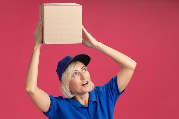 Femme de livraison blonde d'âge moyen impressionnée en uniforme bleu et casquette tenant une boîte en carton au-dessus de la tête en levant isolée sur un mur rose