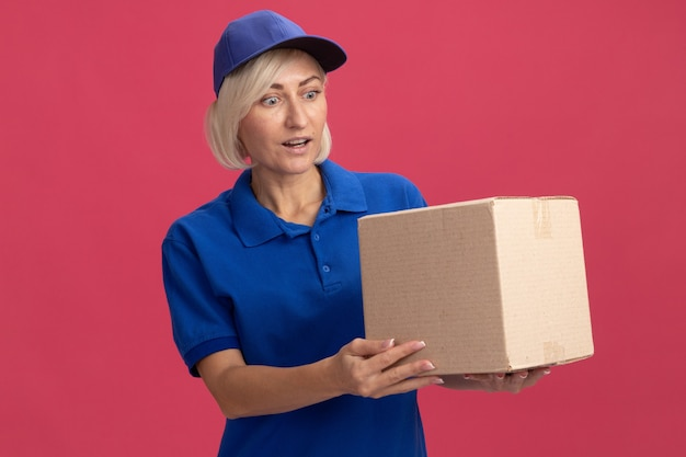 Femme de livraison blonde d'âge moyen impressionnée en uniforme bleu et casquette tenant et regardant une boîte en carton isolée sur un mur rose