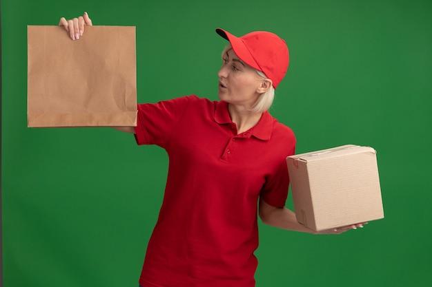 Femme de livraison blonde d'âge moyen impressionnée en uniforme rouge et casquette tenant une boîte en carton et un paquet de papier regardant un paquet de papier