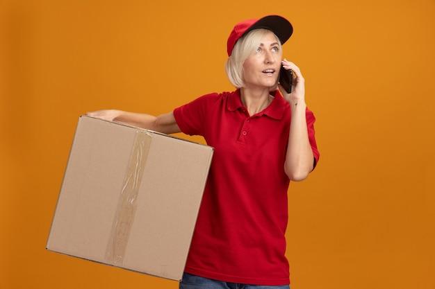 Femme de livraison blonde d'âge moyen impressionnée en uniforme rouge et casquette tenant une boîte en carton parlant au téléphone en levant isolé sur un mur orange avec espace de copie
